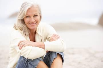 older woman sitting & smiling on beach I cook family dental