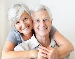Older couple smiling with dental crowns in Birmingham, AL