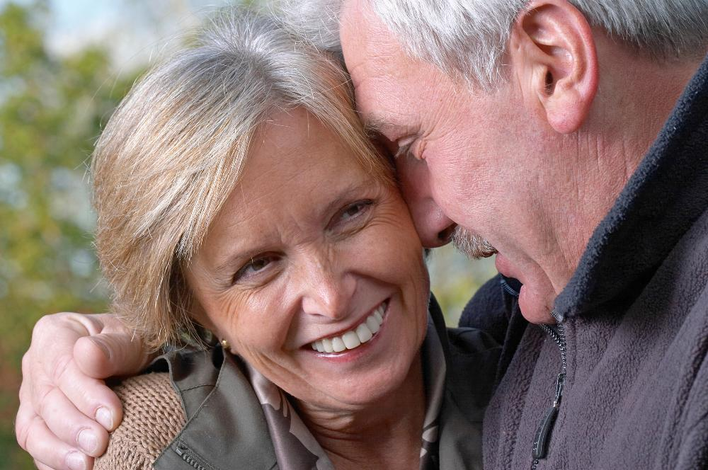 older couple brightly smiling hugging I dental implants at cook family dental