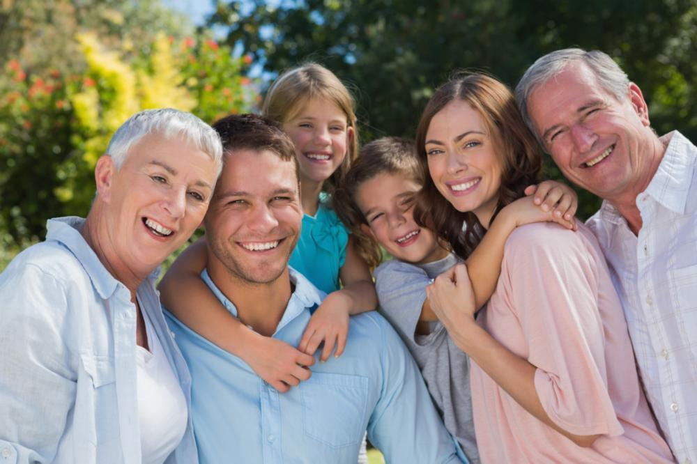 large family grouped together smiling brightly I cook family dental