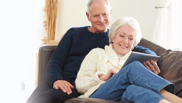 Older couple sitting on a couch l Dental Implants Birmingham AL