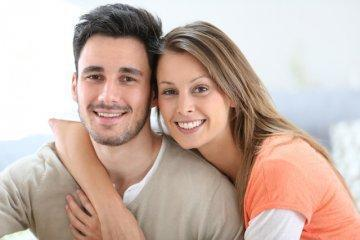 Young couple hugging & smiling l Cosmetic Dentist Birmingham AL